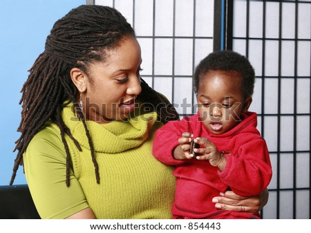 Mother holds her child as he eats a cookie - stock photo