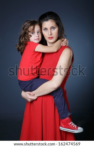Mother holds her little girl in her arms - stock photo