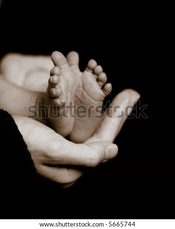 Mother holds her newborn's tiny feet in the palm of her hand. Sepia toned and slight grain for a classic, timeless look. Shallow DOF focus on mother's hand and the toes closest to the viewer.