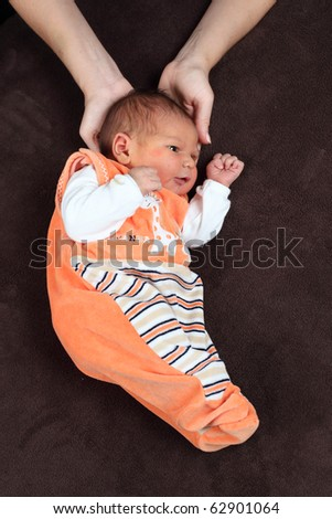 Mother holds newborn baby's head - stock photo