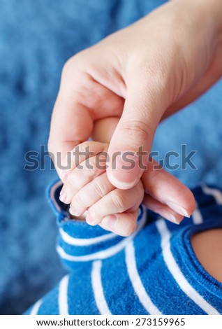 mother holds the hand of a newborn on a blue background - stock photo