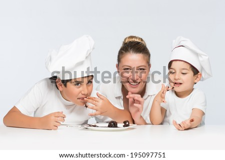 Mother housewife cooking with her kids messing with chocolate and having fun together - stock photo