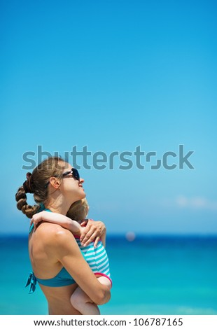 Mother hugging baby on beach