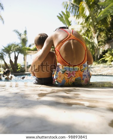 Mother hugging child on edge of swimming pool - stock photo