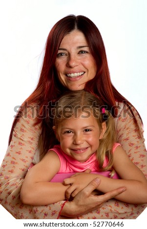 Mother hugging her pretty young daughter and smiling