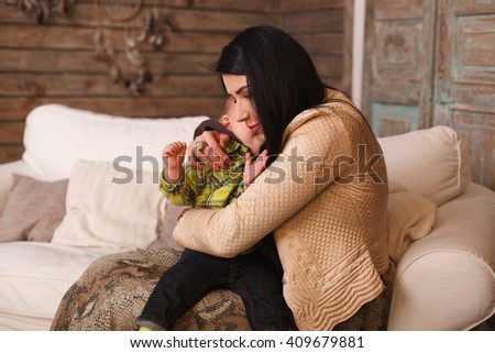 Mother hugging her son, the child poses a funny face. Cute little boy making grimaces, hugs, tenderness, son toddler, holding, sincerity - stock photo