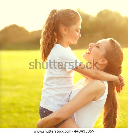 Mother hugging with her little daughter outdoor in nature on sunny day. Sunset