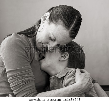 Mother hugs crying 6-year old son, monochrome