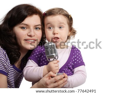 Mother hugs her little daughter, which sings into microphone. - stock photo