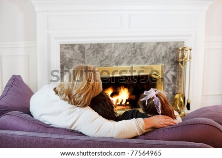 Mother hugs her son and daughter by the fireside