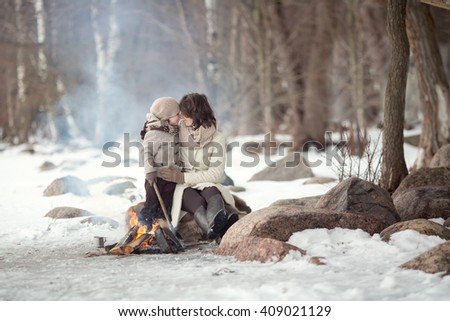 mother in a white coat and brown boots pants hugging her son in a beige jacket, scarf and hat sitting on stones at a fire in a forest. New Year Christmas