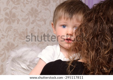 mother in black embracing her little son in white with angelic wings on wall background