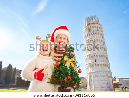 Mother in Christmas hat and daughter in funny reindeer antlers holding Christmas tree in front of Leaning Tour of Pisa, Italy and showing thumbs up. They spending exciting Christmas time traveling. - stock photo