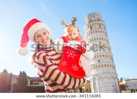 Mother in Christmas hat holding daughter in funny reindeer antlers looking into Christmas sock for a gift. Leaning Tour of Pisa in background. They spending exciting Christmas time traveling Italy - stock photo