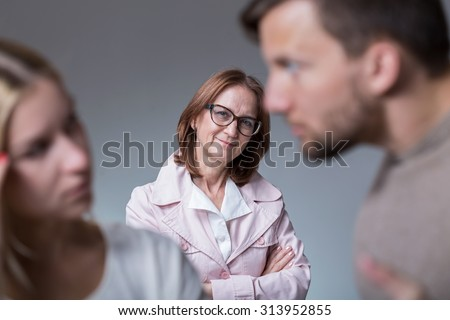 Mother-in-law observing her son and his girlfriend - stock photo