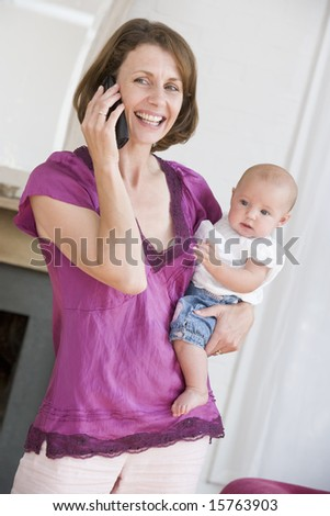 Mother in living room using telephone holding baby smiling - stock photo