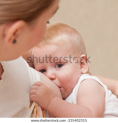 Mother in nursing bra and t-shirt nursing ( breastfeeding ) her baby. Selective focus on baby head - stock photo