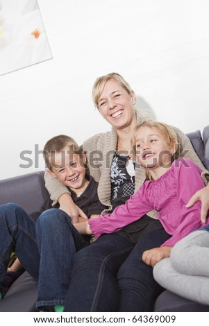 Mother in the sofa with her children - stock photo