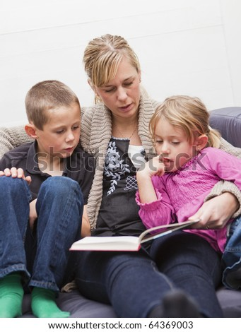 Mother in the sofa with her children reading a book
