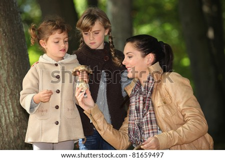 Mother in woods with two daughters - stock photo