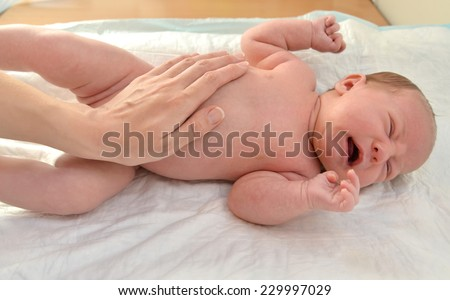 Mother irons the crying baby - stock photo
