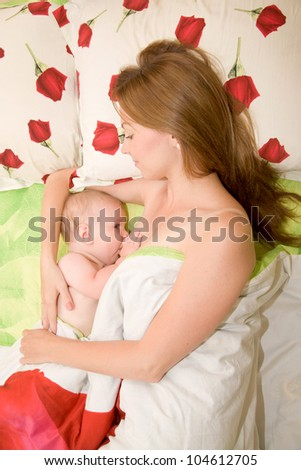 Mother is breast feeding a newborn baby. - stock photo