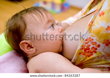 Mother is breast-feeding a newborn baby - stock photo