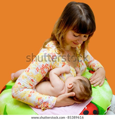 Mother is breast-feeding a newborn baby. Isolated on orange background with clipping path - stock photo