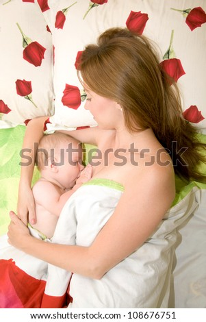 Mother is breast feeding baby in bed. Mother's love. Bedding has a pattern of red roses - stock photo
