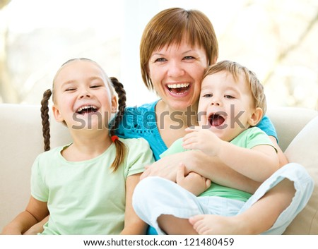 Mother is having fun with her son while sitting on a couch - stock photo