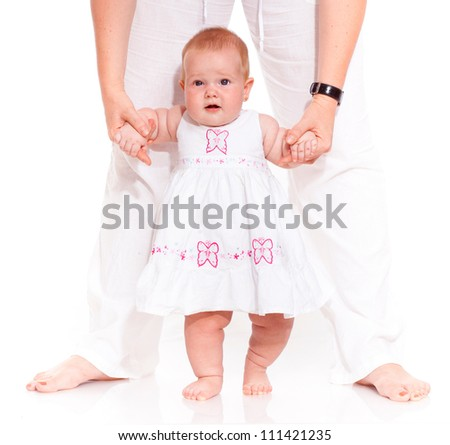 mother is helping her daughter to make first steps - stock photo