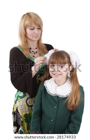Mother is helping her's young daughter prepare to school. Woman is filleting ribbon on girl's hair.  Mom is brushing young schoolgirl's hair. Isolated on white in studio. - stock photo