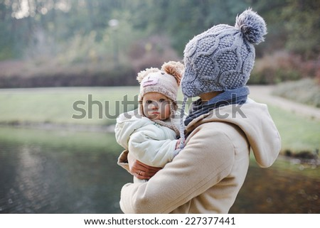 mother is holding her baby in the park with a lake in autumn. - stock photo