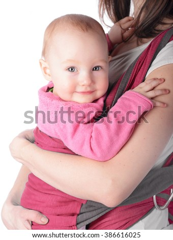 mother is holding her cute baby girl in a pink sling