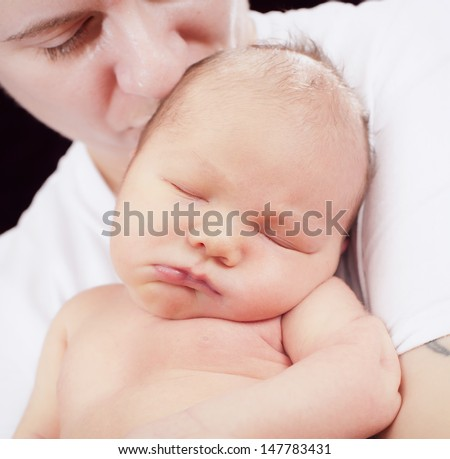 Mother is kissing sleeping baby in the studio