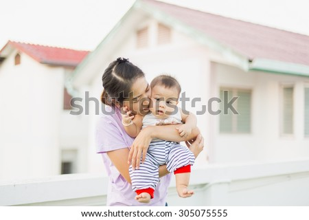 mother is kissing the baby cheeks in the evening - stock photo