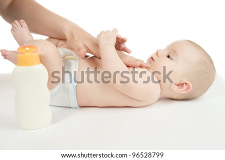 mother is massaging her baby boy - stock photo