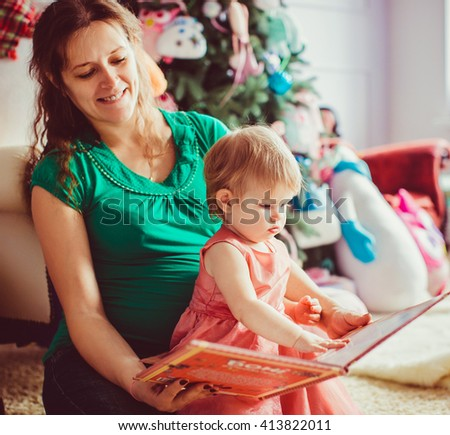 Mother is reading a book for a baby girl - stock photo