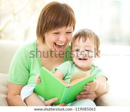 Mother is reading book for her son, indoor shoot - stock photo