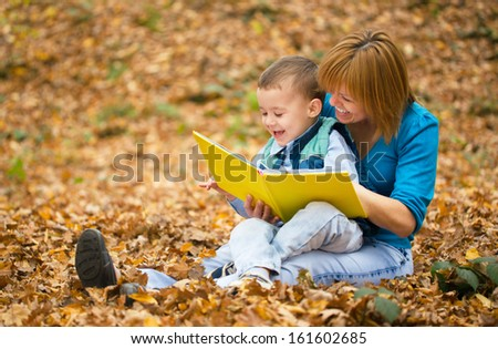 Mother is reading book with her son, outdoor shoot