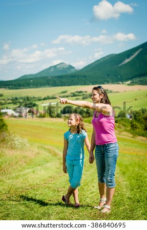 Mother is showing something in distance to her child in nature on sunny summer day - stock photo