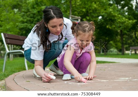 Mother is teaching her cute daughter to draw with chalk on sidewalk - stock photo