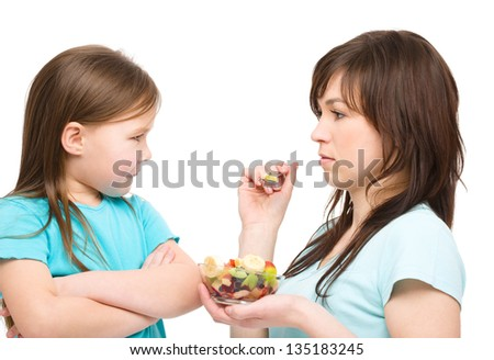 Mother is trying to feed her daughter with fruit salad, isolated over white - stock photo