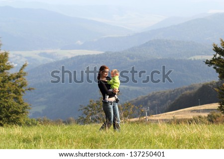 Mother is walking with child on meadow in mountains summer - stock photo