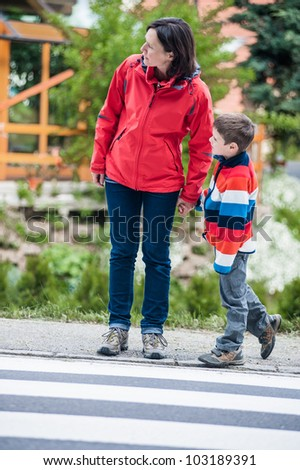 Mother keep looking for cars on the crosswalk - stock photo