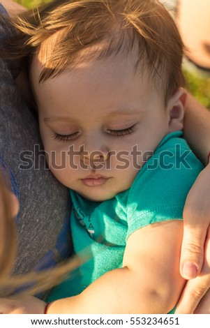 Mother keeps a sleep little baby boy in her arms