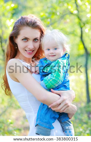 Mother keeps child in her arms on outdoors, smiling and looking at the camera - stock photo