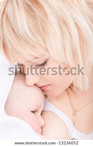 Mother kiss and breast feeding her baby girl - stock photo