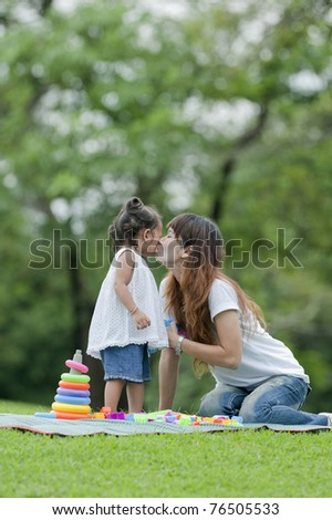 Mother kiss daughter is a small garden. - stock photo