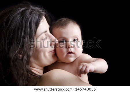 Mother kiss.Mother and baby on Black background - stock photo